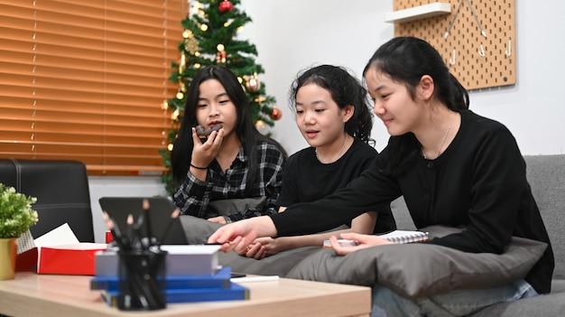 Drie aziatische kinderen die samen thuis een online les hebben met een persoonlijke tutor op een computerlaptop.