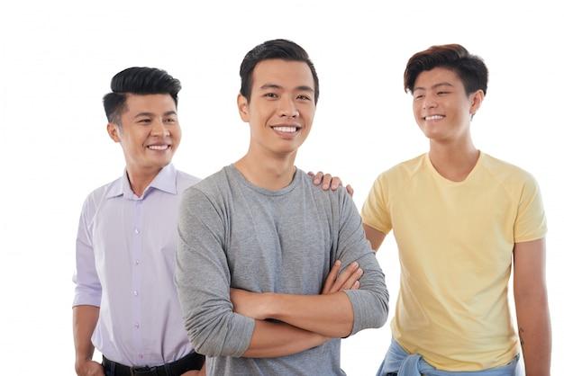 Drie aziatische mannelijke vrienden die samen met hand op schouder stellen