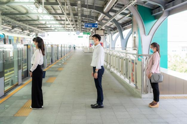 Drie aziatische mensen die een masker dragen op een afstand van 1 meter van andere mensen, houden afstand op afstand tegen covid-19-virussen en mensen die sociaal afstand nemen