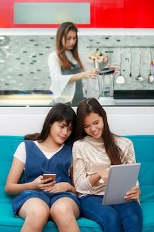 Drie aziatische mensen, dochters spelen en kijken naar smartphone terwijl moeder voedsel voor hen kookt, concept voor problemen in het moderne gezins- en tienerleven