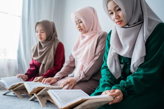 Drie aziatische moslimvrouwen lezen en leren samen het heilige boek van de al-quran