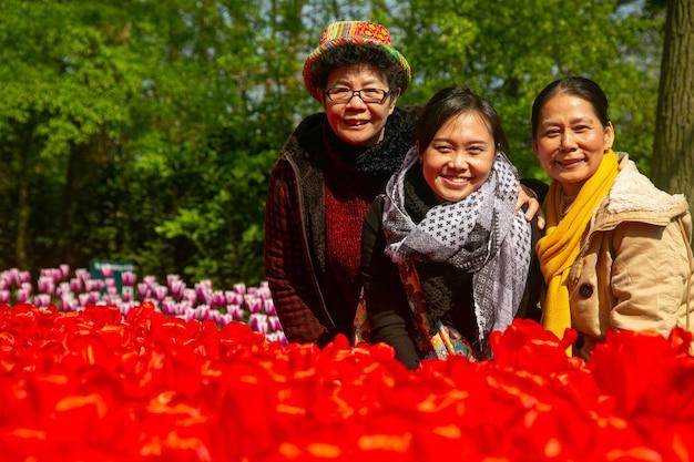 Drie aziatische senior volwassen glimlachen naar de camera in de keukenhof, nederland.