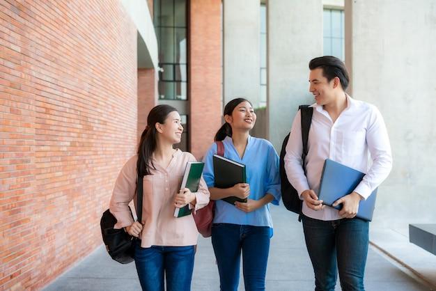 Drie aziatische studenten lopen en praten samen op de universiteit
