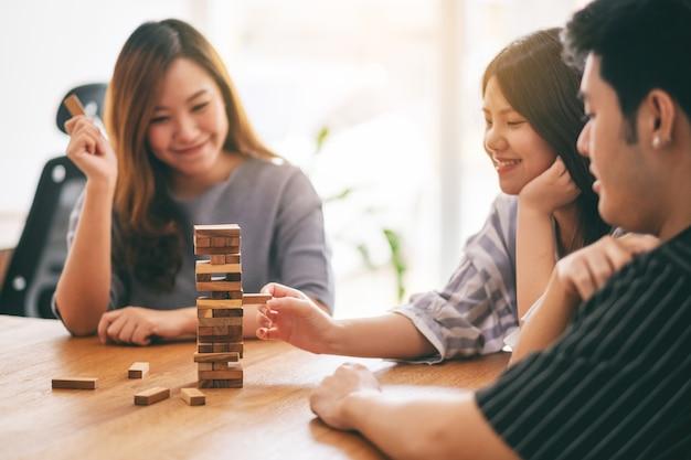 Drie aziatische vrienden die tumble tower houten blokspel zitten en spelen samen met een gelukkig gevoel