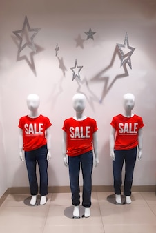 Drie baby-etalagepoppen in een etalage met rode t-shirts met de woorden sale