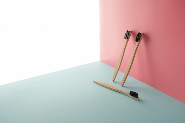 Drie bamboe, houten tandenborstels bevinden zich op een witte, blauwe en roze achtergrond. conceptuele, geometrische compositie met kopie ruimte. geneeskundeconcept, borstelen, milieuvriendelijk, verwerking, compost