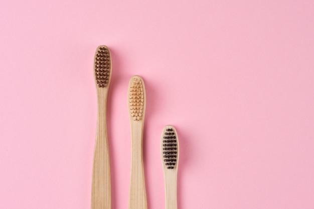 Drie bamboe tandenborstels op roze achtergrond, bovenaanzicht plat lag. geen afval en milieuvriendelijk concept
