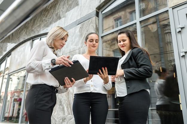 Drie bedrijfsdames met tabletten die zich buiten het gebouw bevinden
