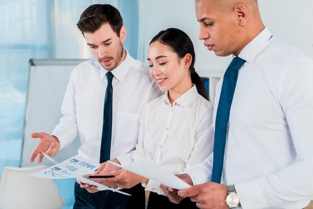 Drie bedrijfsleiders die het businessplan in het bureau bespreken
