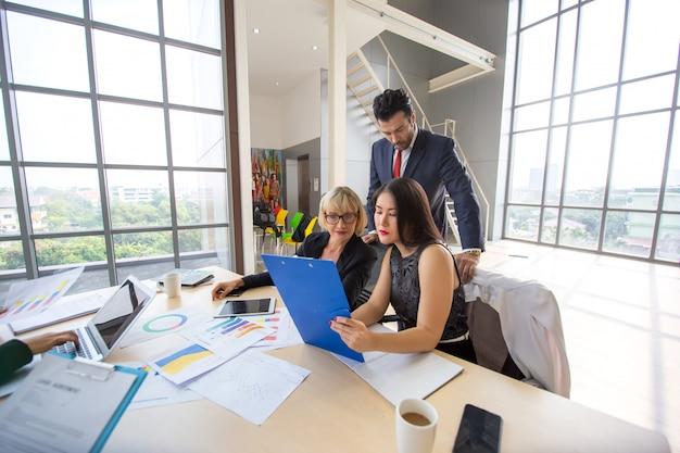 Drie bedrijfsmensen die op gebied kijken en aan een project werken