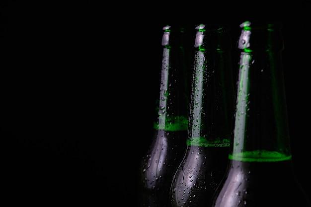 Drie benevelde open flessen koud bier op een zwarte achtergrond.