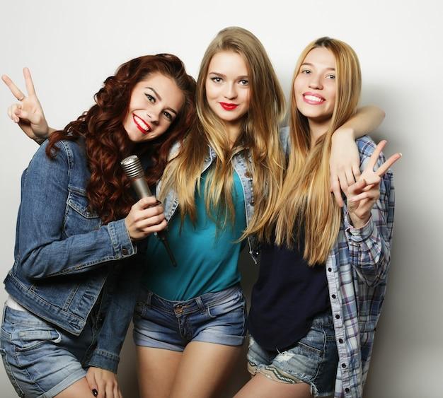 Drie beste vrienden poseren in de studio, gekleed in zomerse outfit en jeansshorts. meisjes glimlachen en plezier hebben.