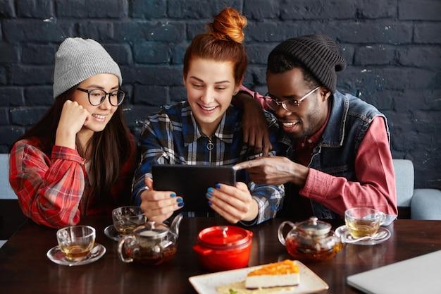 Drie beste vrienden van verschillende rassen die genieten van gratis wifi tijdens de lunch in het restaurant