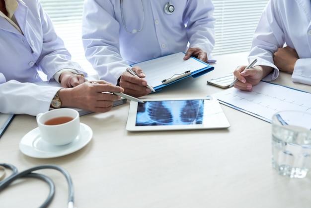Drie bijgesneden artsen analyseren röntgenfoto van de borst op het digitale pad
