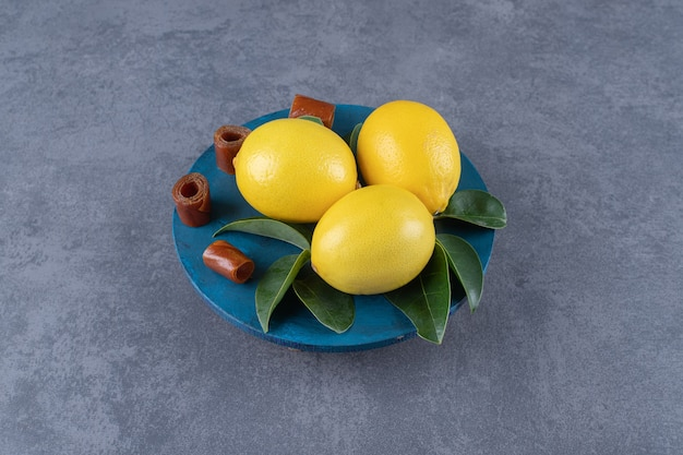 Drie biologische citroenen en bladeren op blauw bord.
