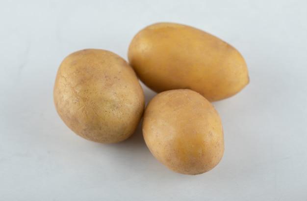 Drie biologische verse aardappelen. close-up foto.