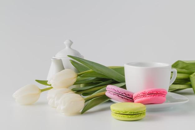 Drie bitterkoekjes, kopje koffie en witte bloemen tulp
