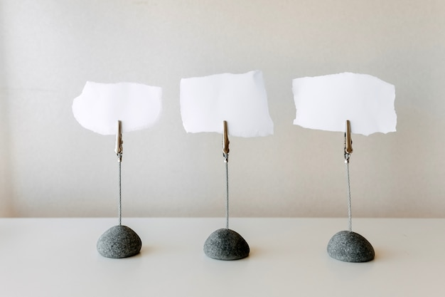 Drie blanco stukjes papier voor het schrijven van notities op een standaard.