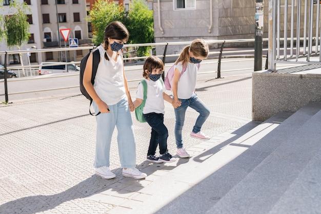 Drie blanke broers van verschillende leeftijden die naar school gaan met maskers op hun gezicht van de coronaviruspandemie covid19