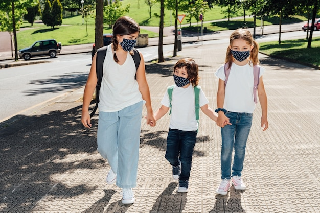 Drie blanke broers van verschillende leeftijden gaan aan het begin van het jaar naar school met maskers op hun gezicht vanwege de coronaviruspandemie covid19