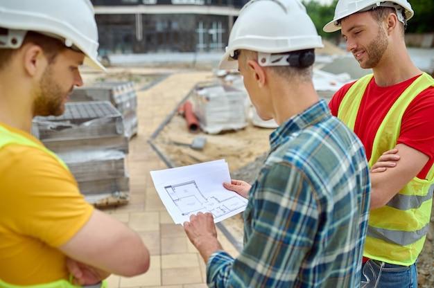 Drie blanke mannen met beschermende helmen die bouwplannen bestuderen