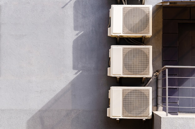 Drie blokken (dozen) airconditioning aan de voorkant van het gebouw.