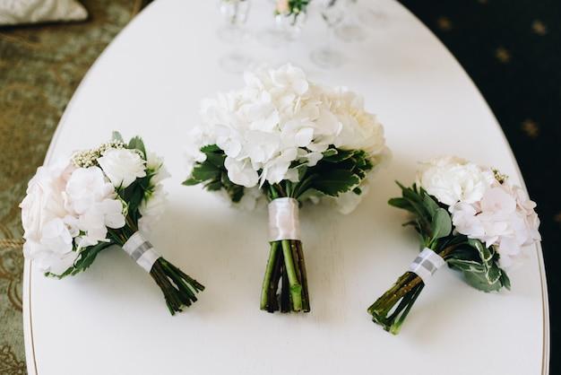 Drie boeketten van witte hortensia liggend op een witte ovale tafel van boven naar beneden