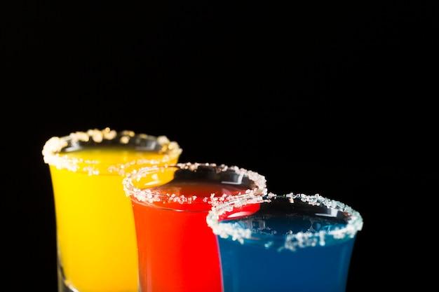 Drie borrelglaasjes met gekleurde cocktail en zoutrand
