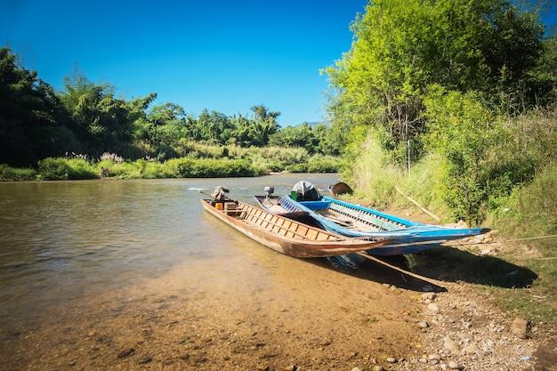 Drie boten werden vastgebonden in de rivier met blauwe hemelachtergrond