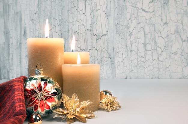 Drie brandende kaarsen met gouden kerstversiering op rustieke neutrale achtergrond