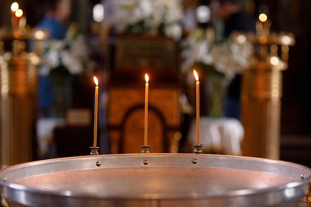 Drie brandende kaarsen op een doopvont voor de doop in een kerk