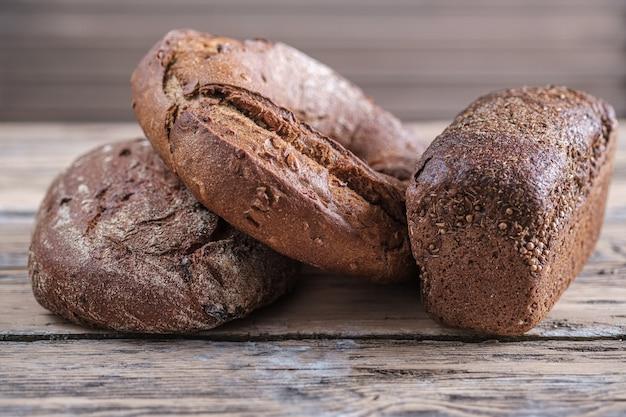 Drie broden rogge-tarwebrood van ronde, ovale en rechthoekige vorm op een houten tafel. zelfgebakken brood