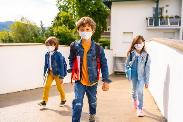 Drie broers met gezichtsmaskers klaar om terug naar school te gaan. nieuwe normaliteit, sociale afstand, coronavirus-pandemie, covid-19. van huis weggaan