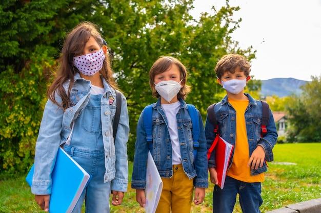 Drie broers met gezichtsmaskers klaar om terug naar school te gaan. nieuwe normaliteit, sociale afstand, coronavirus-pandemie, covid-19. wachten om naar school te gaan met groene planten op de achtergrond