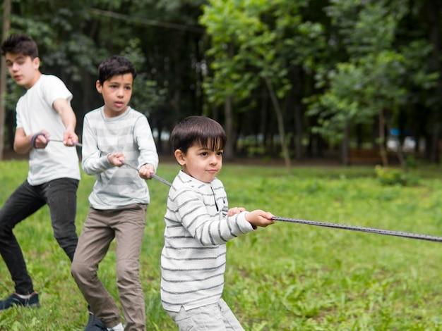 Drie broers spelen met een touw