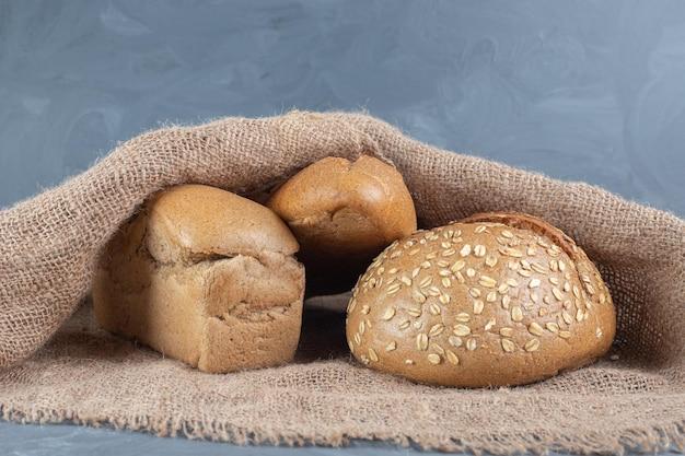 Drie broodbroodjes onder een stoffen bekleding op een marmeren ondergrond.