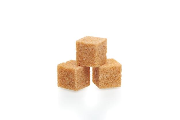 Drie bruine blokjes rietsuiker geïsoleerd op een witte achtergrond. close-up bekijken.