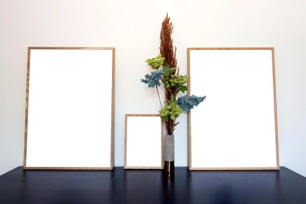 Drie canvasfoto's of fotolijstjes voor kopieerruimte in de buurt van witte muur op houten tafel met decoratief