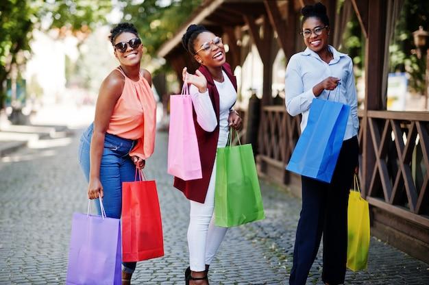 Drie casual afro-amerikaanse meisjes met gekleurde boodschappentassen buiten lopen. stijlvolle zwarte dames winkelen.