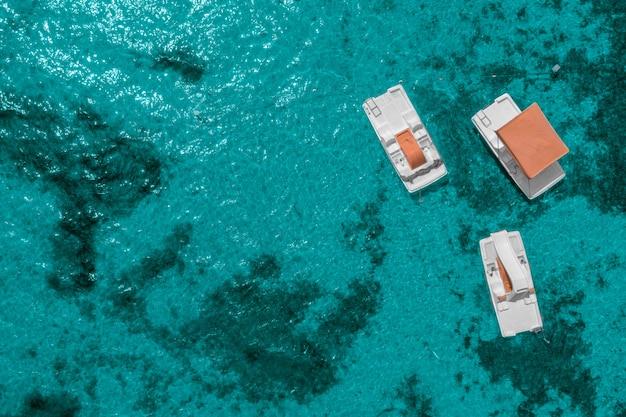 Drie catamarans op het oppervlak van het blauwe zeewater