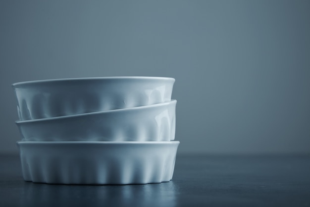 Drie ceramische witte kommen die aan kant van blauwe rustieke lijst en grijze achtergrond worden geïsoleerd