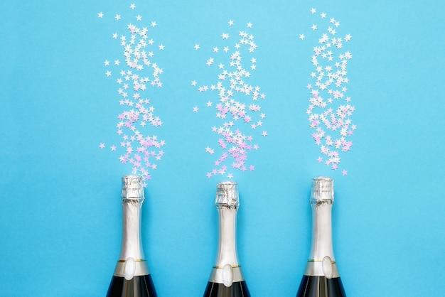 Drie champagneflessen met holografische confetti sterren op heldere blauwe achtergrond. kopieer ruimte, bovenaanzicht. plat leggen van kerstmis, verjaardag, vrijgezellenfeest, nieuwjaarsviering concept.