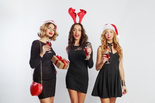 Drie charmante meisjes die tijd doorbrengen op nieuwjaar of kerstfeest. met glas champagne. maskeradehoeden dragen.