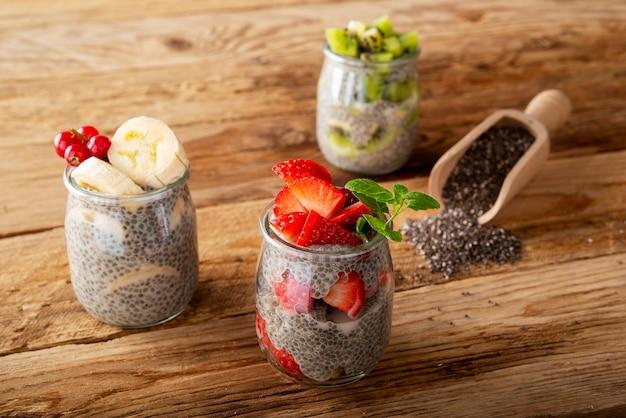 Drie chia-pudding in stawberry de bananenkiwi van de glaskruik op houten plank