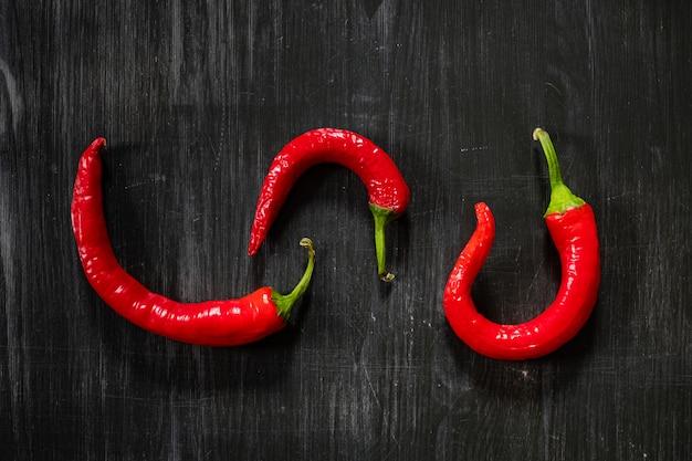 Drie chili pepers op zwarte ondergrond