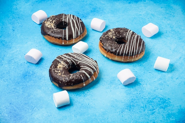 Drie chocolade donuts en marshmallows op blauwe ondergrond.