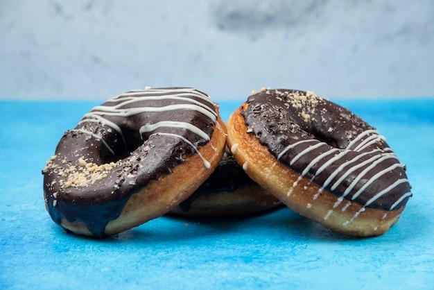 Drie chocolade donuts op blauwe tafel.