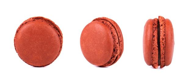 Drie chocolade macarons die op witte ruimte wordt geïsoleerd.