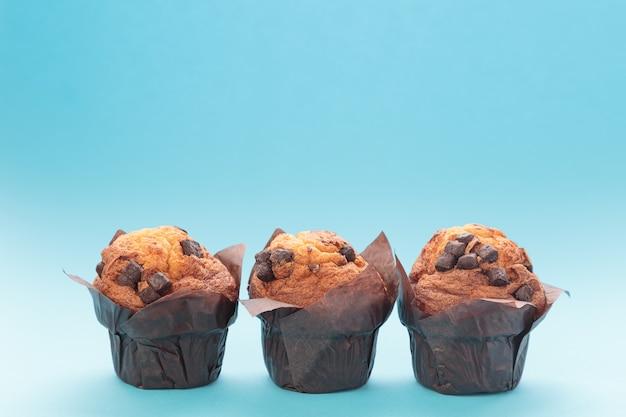 Drie chocolademuffins op een blauwe achtergrond met exemplaarruimte.