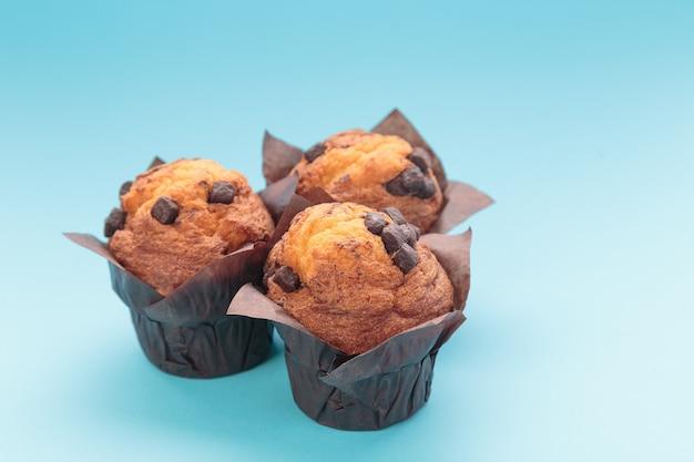 Drie chocolademuffins op een blauwe achtergrond.